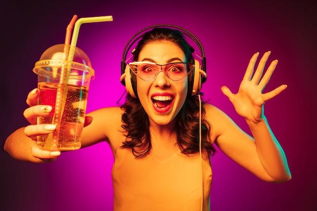 Mulher jovem feliz em óculos de sol vermelhos bebendo e ouvindo música em neon rosa da moda