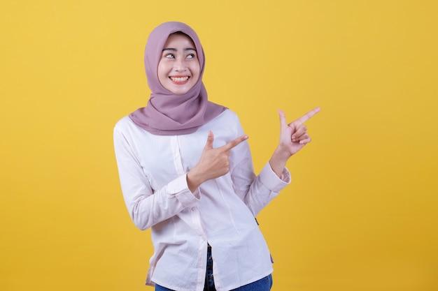 Mulher jovem feliz em pé com o dedo apontando para o lado direito e olhando para cima usando um hijab