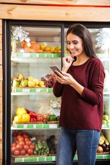 Mulher jovem feliz em pé e usando o celular em uma mercearia