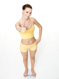 Mulher jovem feliz em pé na balança e mostra o polegar para cima isolado no branco. visão de alto ângulo