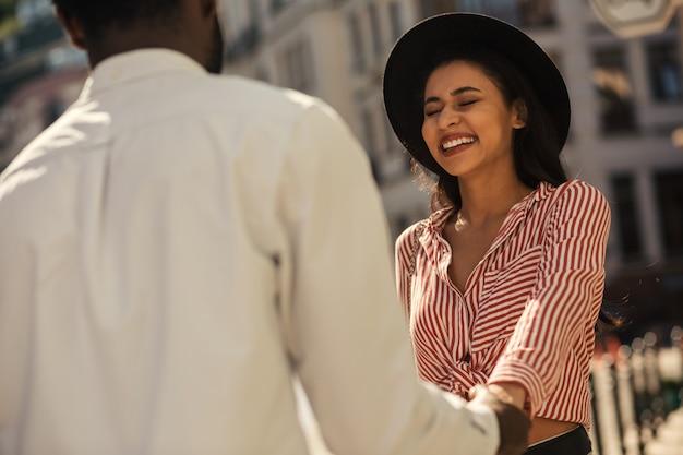 Mulher jovem feliz em pé na rua em um dia ensolarado e fechando os olhos enquanto ria. namorado segurando a mão dela