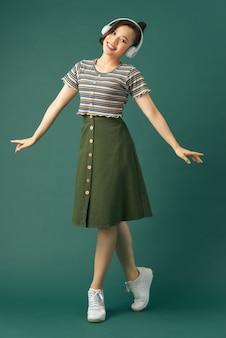 Mulher jovem feliz em pé sobre uma perna, ouvindo música em fones de ouvido e cantando