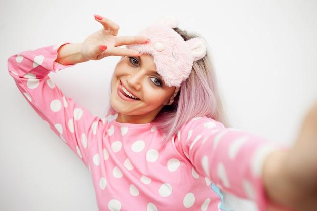 Mulher jovem feliz em pijama e máscara de dormir. acordei de manhã