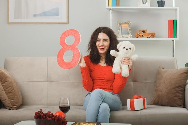 Mulher jovem feliz em roupas casuais, sentada em um sofá com o número oito segurando o ursinho de pelúcia, olhando para a câmera, sorrindo alegremente na luz da sala de estar, comemorando o dia internacional da mulher, 8 de março
