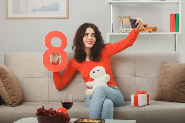 Mulher jovem feliz em roupas casuais, sentada em um sofá com o presente segurando o número oito e o ursinho de pelúcia fazendo selfie usando smartphone, sorrindo, comemorando o dia internacional da mulher, 8 de março.