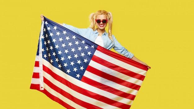 Mulher jovem feliz em roupas jeans, segurando a bandeira dos eua isolada em fundo amarelo