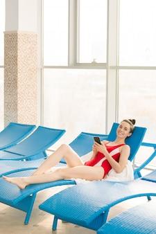 Mulher jovem feliz em trajes de banho vermelho relaxante na espreguiçadeira depois de nadar no centro esportivo contemporâneo