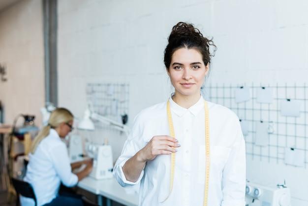Mulher jovem feliz em trajes de trabalho brancos olhando para você enquanto está em uma grande oficina contemporânea com máquinas de costura