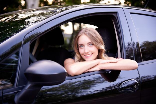 Mulher jovem feliz em um automóvel preto.