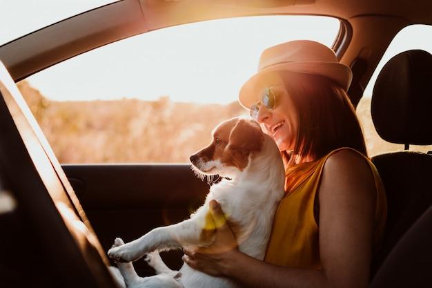 Mulher jovem feliz em um carro com seu cachorro ao pôr do sol