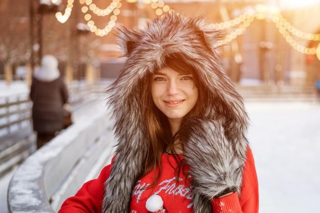 Mulher jovem feliz em um chapéu de lobo no inverno na pista de gelo posa com um suéter vermelho do lado de fora à tarde