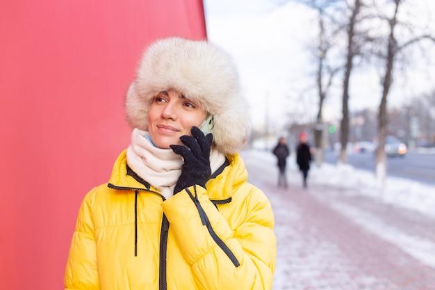 Mulher jovem feliz em um fundo de uma parede vermelha com roupas quentes em um dia ensolarado de inverno, sorrindo e falando ao telefone em uma calçada de uma cidade nevada