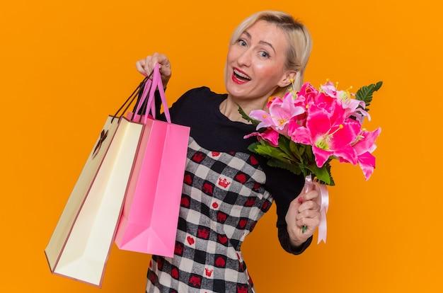 Mulher jovem feliz em um lindo vestido segurando um buquê de flores e sacolas de papel com presentes sorrindo alegremente, comemorando o dia internacional da mulher em pé sobre a parede laranja