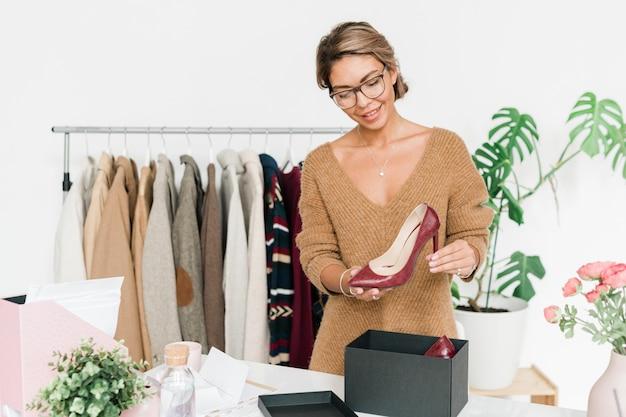 Mulher jovem feliz em um pulôver de malha casual elegante em pé ao lado da mesa, segurando um sapato da moda de salto alto