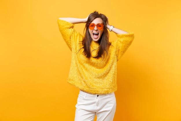 Mulher jovem feliz em um suéter de pele, calça branca, óculos coração laranja agarrados à cabeça, gritando isolado em fundo amarelo brilhante. emoções sinceras de pessoas, conceito de estilo de vida. área de publicidade.