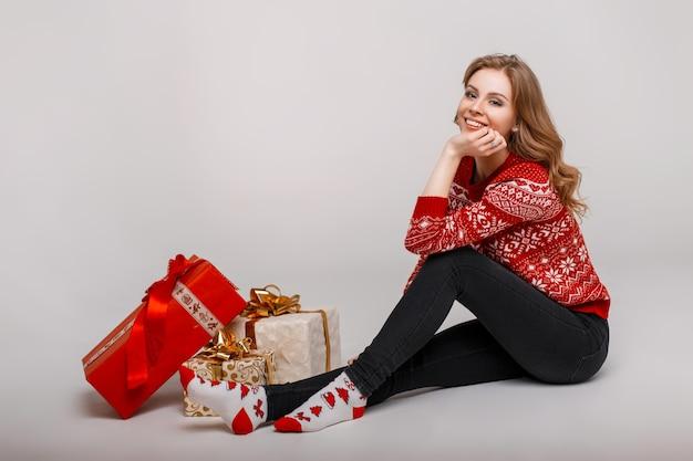 Mulher jovem feliz em um suéter vermelho da moda com meias sentado perto de presentes em estúdio