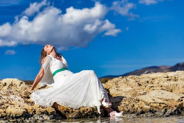 Mulher jovem feliz em um vestido branco sentada na rocha de areia e curtindo na praia de elafonisi