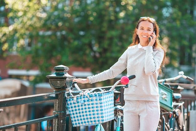 Mulher jovem feliz em uma bicicleta na rua falando ao telefone
