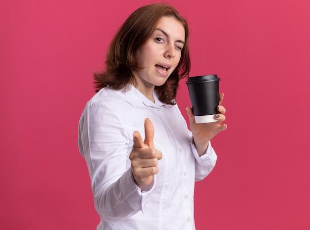 Mulher jovem feliz em uma camisa branca segurando uma xícara de café apontando com o dedo indicador na frente, sorrindo e piscando em pé sobre a parede rosa