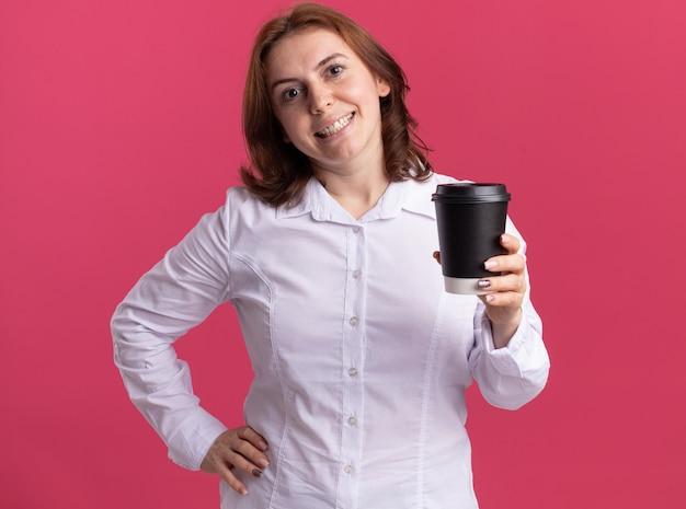 Mulher jovem feliz em uma camisa branca segurando uma xícara de café, olhando para a frente, sorrindo alegremente em pé sobre a parede rosa
