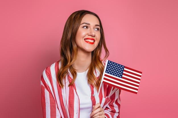Mulher jovem feliz em uma camisa vermelha com batom vermelho mantém uma pequena bandeira americana e sorrisos isolados sobre o espaço rosa, bandeira dos eua, 4 de julho dia da independência
