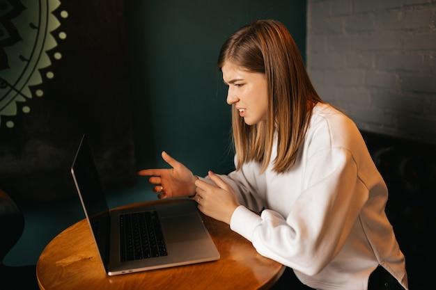 Mulher jovem feliz em uma chamada de vídeo através de um computador laptop, sentado à mesa em um restaurante, acenando com as mãos.