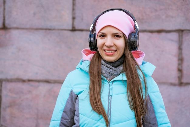 Mulher jovem feliz em uma jaqueta quente e chapéu rosa, ouvindo música em fones de ouvido contra o background.