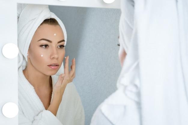 Mulher jovem feliz em uma toalha na frente do espelho aplica creme para o rosto, um conceito de cuidados com a pele em casa