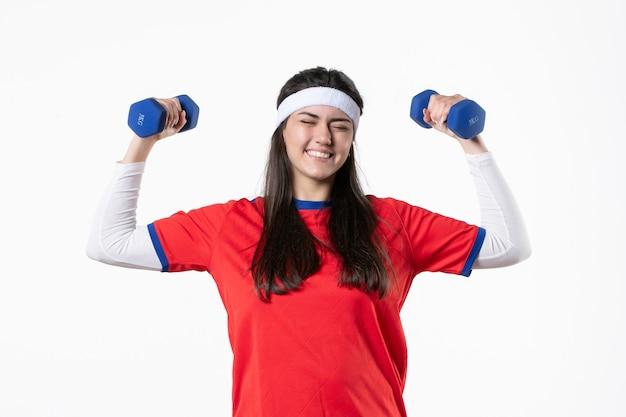 Mulher jovem feliz em vista frontal com roupas esportivas, malhando com halteres
