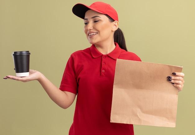 Mulher jovem feliz entregadora de uniforme vermelho e boné segurando um pacote de papel, olhando para a xícara de café com um sorriso no rosto em pé sobre a parede verde