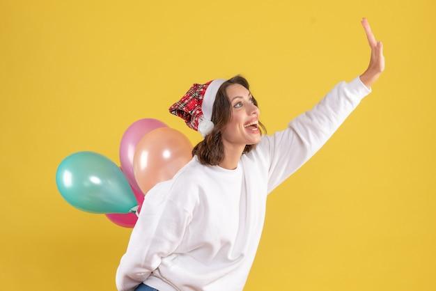 Mulher jovem feliz escondendo balões coloridos ano novo natal cor férias mulher emoções