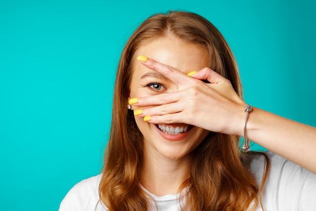 Mulher jovem feliz espiando por entre os dedos e sorrindo
