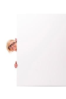 Mulher jovem feliz espiando por trás do quadro branco