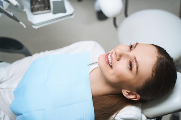 Mulher jovem feliz está indo ao médico e deitada na cadeira odontológica enquanto espera o exame