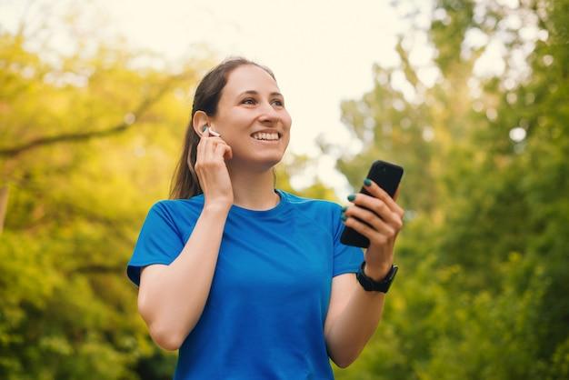 Mulher jovem feliz está ouvindo algo em seus fones de ouvido sem fio.