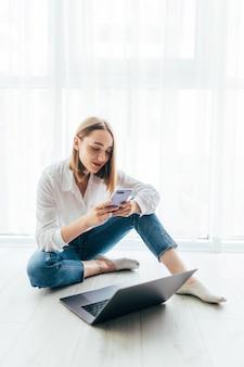 Mulher jovem feliz, estudando em casa, lendo um sms ou mensagem de texto no celular com um sorriso, sentada no chão com um laptop
