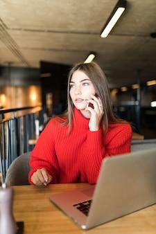 Mulher jovem feliz falando ao celular e usando o laptop no café