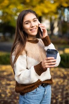 Mulher jovem feliz falando ao telefone, segurando uma xícara de café para viagem e sorrindo.