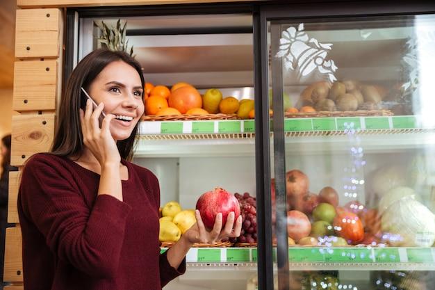 Mulher jovem feliz falando no celular e comprando romã no supermercado