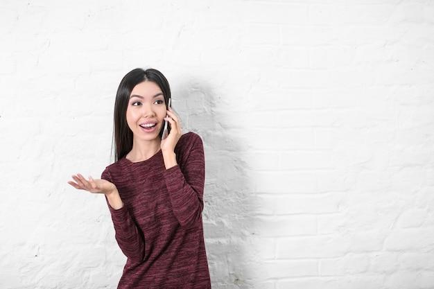 Mulher jovem feliz falando no celular perto de uma parede branca