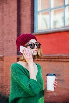 Mulher jovem feliz falando no telefone celular e segurando café na rua da cidade