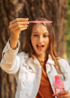 Mulher jovem feliz fazendo bolhas de sabão
