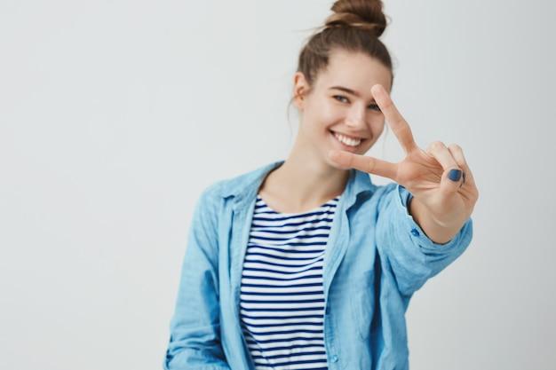Mulher jovem feliz, fazendo o gesto de vitória com os dedos, sinal de v