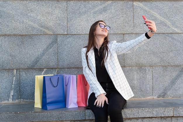 Mulher jovem feliz fazendo selfie com bolsas coloridas