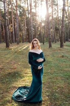 Mulher jovem feliz grávida caminhando ao ar livre na floresta