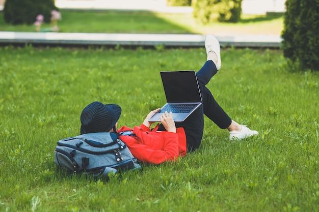 Mulher jovem feliz hipster trabalhando em computadores portáteis. rapariga estudante usando laptop no campus universitário