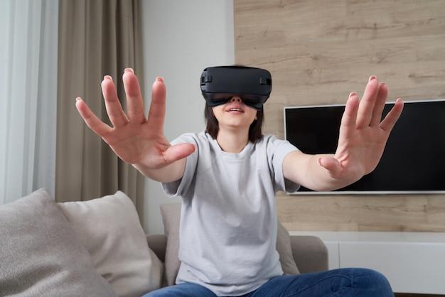 Mulher jovem feliz jogando em óculos vr interior, conceito de realidade virtual com jovem se divertindo com óculos de ouvido,