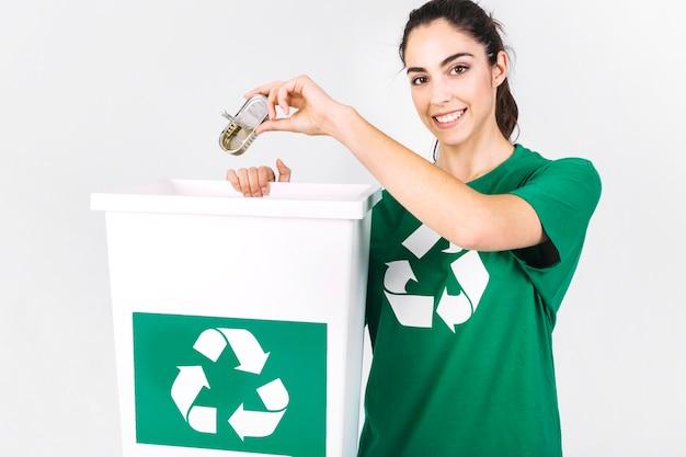 Mulher jovem feliz jogando mini tiffin caixa em reciclar o caixote do lixo
