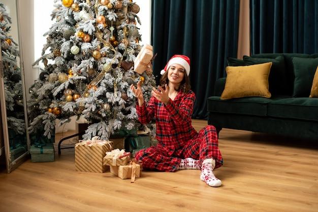 Mulher jovem feliz jogando um presente perto da árvore de natal. ela está sentada perto de presentes e presentes. tendências em cores fortuna ouro e maré verde.