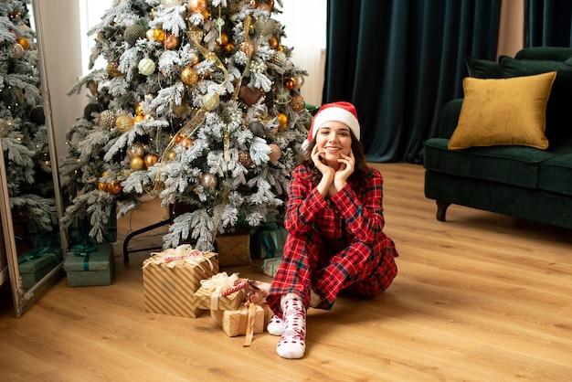 Mulher jovem feliz jogando um presente perto da árvore de natal. ela está sentada perto de presentes e presentes. tendências em cores fortuna ouro e verde maré.